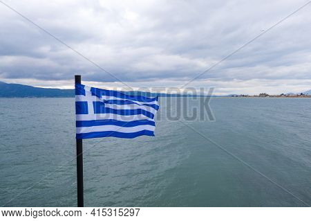 Greek Flag Waves On Sea Water And Cloudy Blue Sky.