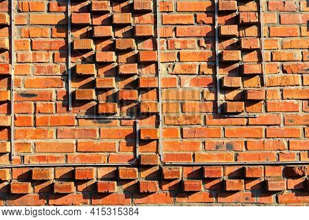Background Of Red Brick Wall Texture. Close-up View Of Cement Bonded Brick Wall. An Ancient Red Bric