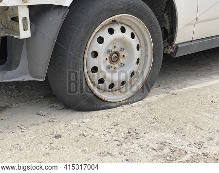 Voronezh, Russia April 2, 2021: Car With Deflated Wheel On Street. Old Gray Car With Deflated Wheel
