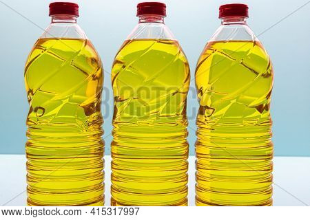 Plastic Bottles With Edible Soy Oil On Blue Background. Vegetable Oil. Soy Oil Is A Type Of Vegetabl