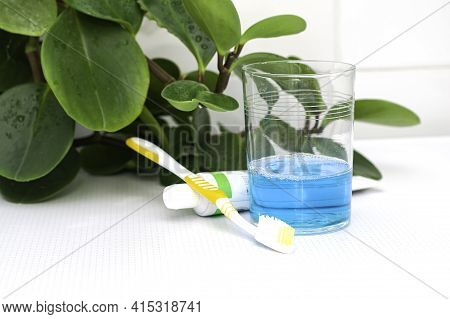 A Glass Of Mouthwash A Toothbrush And Toothpaste On The Bathroom Table In The Background A Houseplan