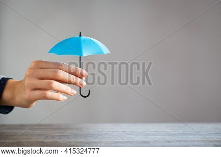 Close up hand of woman holding small umbrella on table with copy space. Woman holding small light blue umbrella as sign of protection on desk against grey wall. Girl protect something on table.