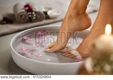 Close up of woman soaking her feet in grey bowl of water with floating petals at beauty luxury spa. Detail of woman feet at wellness center on pedicure procedure. Foot spa and body care concept.
