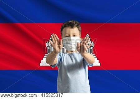 Little White Boy In A Protective Mask On The Background Of The Flag Of Cambodia Makes A Stop Sign Wi