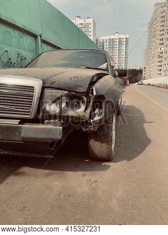 Close Up Of Broken Car On Side Of Road. Damaged Bumper, Headlight And Bodywork Of Black Car After Ac