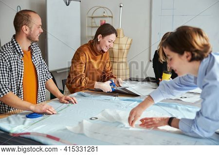 Cheerful Couturiere Laughing While Cutting Fabric Material