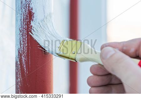 Worker's Hand With Brush That Painting Metal Construction Or Pipes.