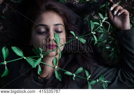 A creeper plant touching sleeping woman's face in the wild. Close up of a beautiful young Indian girl laying down on the grass, with green creeper running over her face.