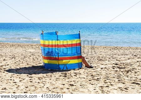 Two People Relaxing Behind Colorful Striped Windscreen On The Beach Near The Sea