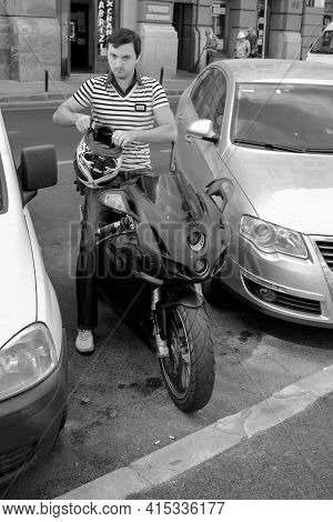 Timisoara, Romania - August 15, 2012: Man Sitting On His Bike And Putting His Helmet. Real People. B