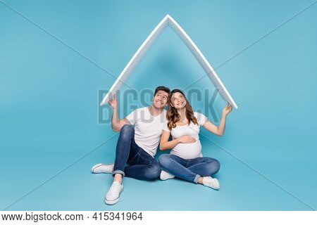 Full Size Photo Of Young Happy Positive Couple Pregnant Wife And Husband Look Up Isolated On Blue Co