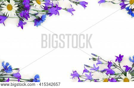 Frame Of Violet Flowers Bellflowers, Chamomiles And Blue Cornflowers On A White Background With Spac