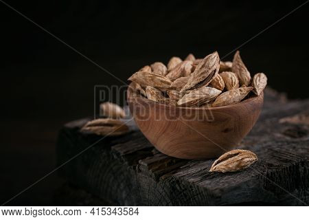 Pile Of Almond Nuts In A Bowl On A Dark Wooden Background. Fresh Nuts In Their Shells.