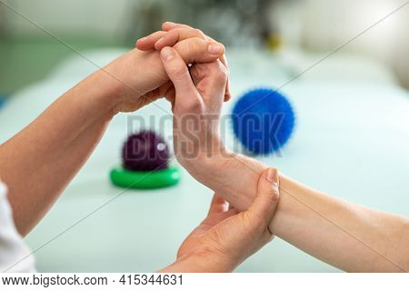 Doctor Exercising And Making Rehabilitation With Patient Wrist