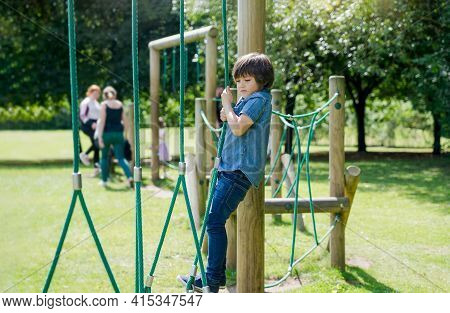 Active Kid Holding Robe In Playground, Child Enjoying Outdoors Activity In A Climbing Adventure Park
