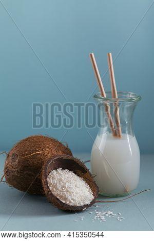 Bottle Of Coconut Vegan Milk With Straws, Whole Coconut And Flakes On Light Blue Background. Healthy