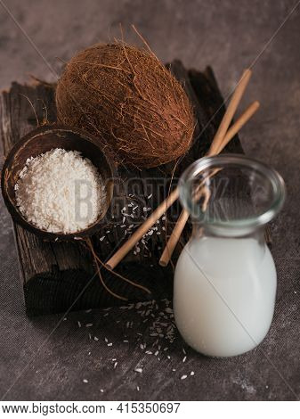 Bottle Of Coconut Vegan Milk With Straws, Whole Coconut And Flakes On Dark Background. Healthy Lifes