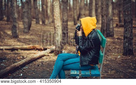 Young Woman In Casual Clothes Sitting On Bench And Photographing On Old Photo Camera In Forest. Fema