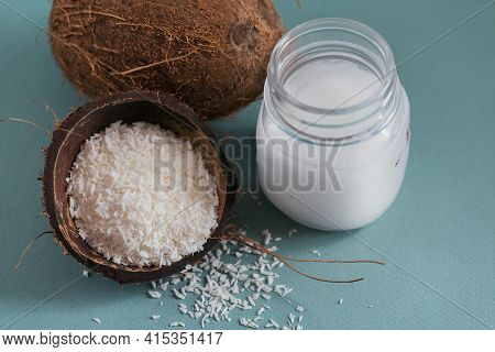 Coconut, Coco Flakes And Coconut Oil In Jar On Light Blue Background. Healthy Cooking Concept