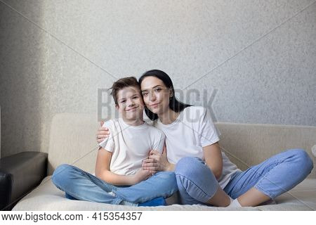 A Happy Brunette Mom In A White T-shirt And Jeans Hugs Her Loving Son Sitting At Home On The Couch.