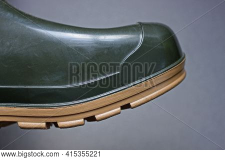 Part Of A Green Rubber Boot With A Brown Sole On A Gray Background