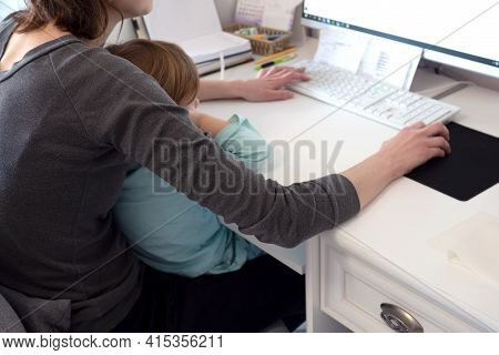 Mother Multi-tasking, Holding Girl Kid And Using Computer At Home. Candid Authentic And Real Life Mo