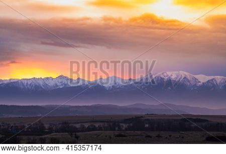 Dramatic Early Sunrise Landscape Over Carpathian Mountains Covered In Snow With Beautiful Orange Sky