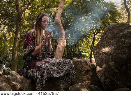Caucasian Woman With Dreadlocks Lighting Incense In Nature