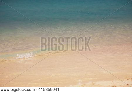 Wave Of Blue Turquoise Sea Water Splash On White Sandy Beach In A Bright Day Light. Tropical Sandy B