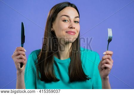 Portrait Of Hungry Woman With Fork And Knife. Lady Waiting For Serving Dinner Dishes With Cutlery On