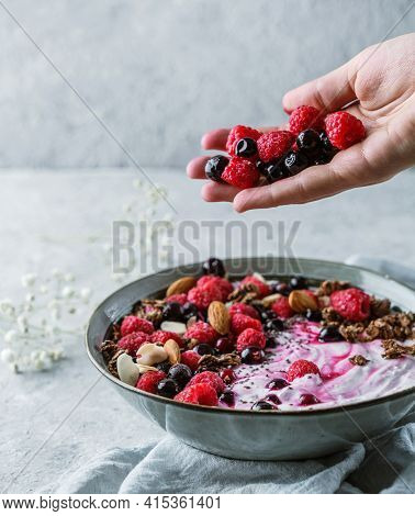 Hand Throws Berries In Bowl With Yogurt, Granola, Muesli, Seeds, Frozen Raspberries, Nuts On Light B