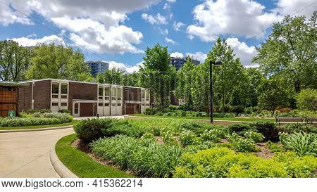 Outside Outdoor Plaza Terrace Adorned With Plants And Trees In Summer Under A Blue And Cumulus Cloud