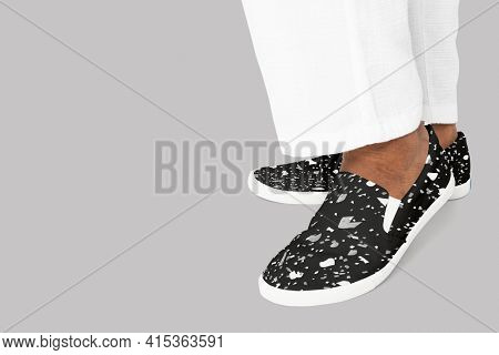 Black slip-on shoes with abstract design casual apparel close up with design space