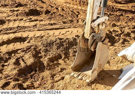 Backhoe Scoop Shovel Attachment, Used On Backhoe For Moving Soil Or Gravel, Is Resting On The Dirt A