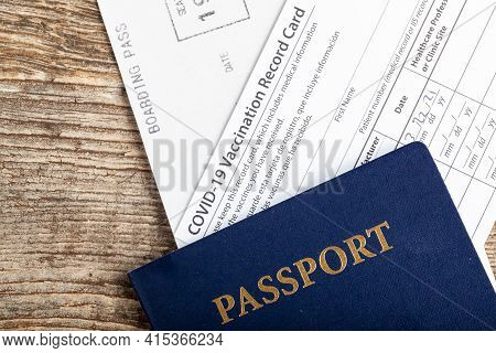 Flat Lay Top View Image Showing A Passport, A Boarding Pass And A Covid-19 Vaccination Record Card P