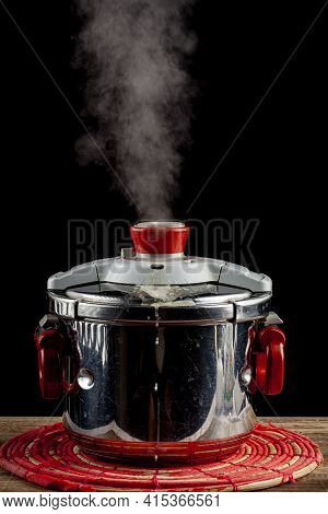 A Steel Pressure Cooker Is Cooling On A Fabric Trivet On Wooden Table. The Pressure Valve Is Release