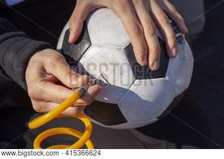 Close Up Image Showing A Caucasian Woman Holding A Soccer Ball And Inserting Needle Bit At The End O