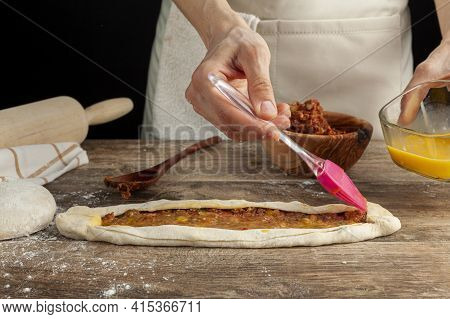 Close Up Image Of A Woman Spreading Homogenized Raw Egg On Top Of Turkish Kiymali Pide Recipe As A T