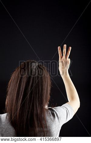 Behind The Head View Of A Young Caucasian Woman With Long Brown Hair Wearing Short Sleeve Shirt Agai