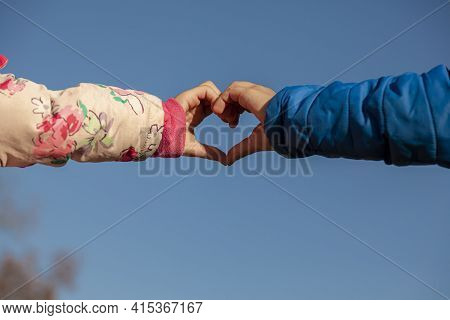 A Cute Abstract Image Showing The Touching Hands Of A Girl With Pink Coat And A Boy With Blue Coat.