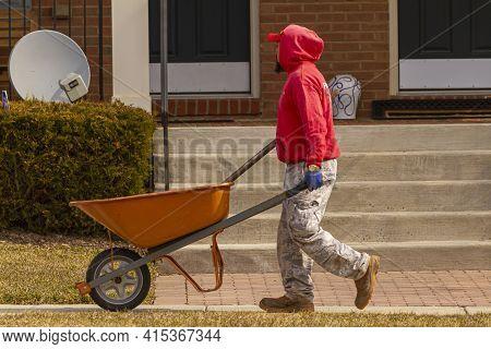 Clarksburg, Md, Usa 03-03-2021: A   Hispanic Gardener Is Carrying An Empty Wheel Barrow In A Residen