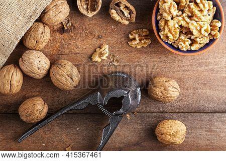 Flat Lay Image Showing A Cast Iron Walnut Pliers ( A Nutcracker Tool) With Raw Fresh Walnuts In Shel