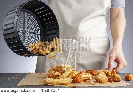 A Woman Is Dumping Fresh Made Potato Waffle Fries From Basket Onto A Countertop Together With Chicke