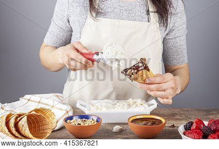 A Woman Chef Is Scooping Homemade Vanilla Ice Cream Onto Handmade Waffle Ice Cream Cones. She Dipped