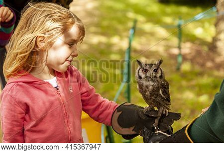 Oxford, Uk 05-22-2011: A Pretty Little Caucasian Girl With Ginger Hair Is Holding A Tiny Baby Bubo B