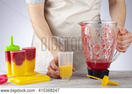 A Mother Is Preparing Homemade All Natural Fruit Popsicles. She Is Filling Bpa Free Plastic Molds Wi
