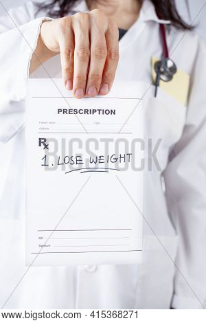 A Caucasian Female Physician In White Coat Is Prescribing Lose Weight To An Obese Or Overweight Pati