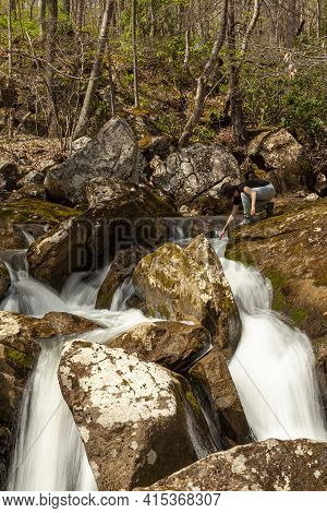 A Hiker Woman Is Trying To Touch The Water On Top Of A Waterfall. A Long Exposure Shoot At A Rural L