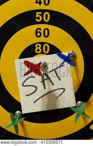 A Dart Board With Multiple Arrows. The Red Arrow Hits The Bullseye. A Note That Says Sat Is Undernea