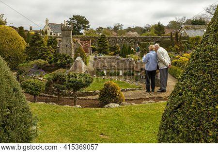 Isle Of Wight, Uk 04-25-2010 Elderly Caucasian Couple Is Visiting The Famous Godshill Model Village.